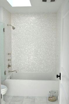 Ein ganz weißes Badezimmer ist mit Sechseck Mutter Perlmutt Fliesen, die die Wanne Zone abheben