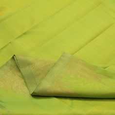 This handwoven #silk sari borrows its vibrant colour from the lime green hue. The shot silk body is a delicate mix of yellow and green reflecting magical nuances in changing lights. The simple zari border is made up of a row of temple motifs. The pallu is a splash of oversized and dramatic temple motifs in lime green on a gold canvas. A plain green blouse with single temple border adds the perfect foil to this #Sarangi. For Kanjivarams in this alluring green, visit Sarangi. Code 070126583.