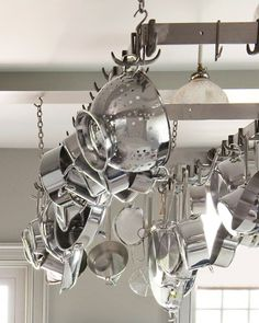 "Use a Hanging Rack to save space in the kitchen, ""Using a rack will save so much space in your cabinets -- and make your pots and pans easier to find. Martha hangs hers above the stationary island near the range."""
