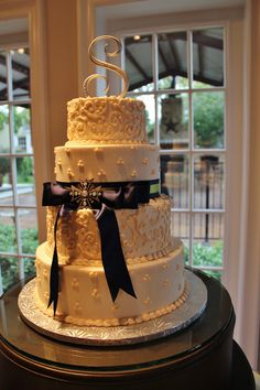 White on white wedding cake with a touch of navy and green.  By Rockwall Wedding Chapel, Rockwall, TX www.rockwallchapel.com