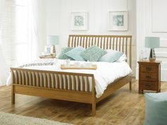 The Orion oak bed frame follows a sleigh-bed design, yet with an unusual modern twist.