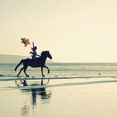 Girl with balloons riding along the beach.