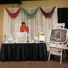 8' x 10' Pipe and Drape backdrop dressed with white voile, fairy lights and accent swags. Rental offered by Moments In Time Wedding & Event Rentals ~ 406.208.9549.  Backdrop design for Top Tier Cakes at 2015 Billings Hotel Bridal Fair.