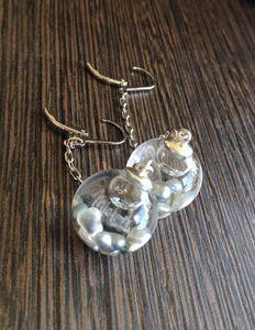 BOUCLES D'OREILLES BULLES Les boucles bulles EI AO signifient naissance du monde, de la lumière en tahitien. Elles vous offrent un bout de rêve…  - Keishis de Tahiti  - Bulle de verre: 16 mm  - Dimension apprêt ovale en rhodium: 19x45 mm  - Apprêt et chaînette en argent rhodié   Bijou made in Tahiti. Livré avec une boîte nacrée explicative du concept de bulle EI AO. A l'occasion de voyages en avion, le bijou doit vous accompagner en cabine.