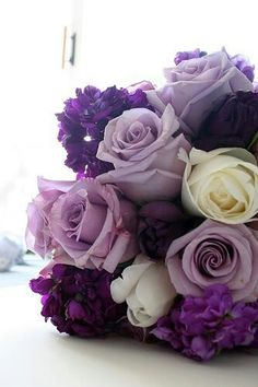 """Dark Purple, Plum and Lavender with white accents. Dark purple flowers are """"Stock"""" with various shades purple roses."""