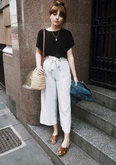 10 looks do Instagram para inspirar seu fim de semana. T-shirt preta, calça pantacourt, flat mule marrom, bolsa de palha
