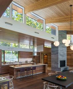 This modern kitchen has dark wood cabinets with white countertops, while a large island provides an additional place for seating. Modern Wood House, White Countertops, Kitchen Countertops, Contemporary Interior Design, House In The Woods, Design Case, Dining Area, Kitchen Remodel, Kitchen Design