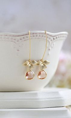 These beautiful long dangle earrings feature delicate matte gold orchids and champagne colored glass teardrops dangling freely from gold plated long oval