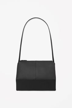 Made from panels of structured leather, this shoulder bag is a modern geometric shape. Fully lined in cotton, it has a removable leather strap, in-lining pocket and a simple zip fastening.