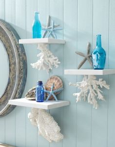 Bathroom shelving inspired by the sea. If I were to replicate this I would cut wooden boards the length I wanted, paint them white and securely attach them to the wall. Then I would find plastered coral, paint it white and attach under the shelves. I love the white / ocean blue decor that 'pop' against the light blue walls. Super cute!