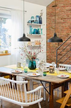 Cheerful kitchen dining with a brick wall and blue glass jar accents.  via La Bici Azul Blog