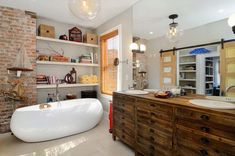 Modern eclectic bathroom with exposed brick wall rustic wooden vanity and ample shelf space Seasonal Style: Hot Bathroom Trends to Try Out this Summer Eclectic Bathroom, Rustic Bathroom Vanities, Wood Bathroom, Bathroom Interior, Modern Bathroom, Bathroom Shelves, Bedroom Vanities, Bathroom Remodeling, Master Bathroom
