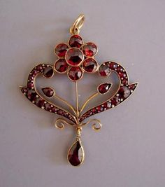 "BOHEMIAN garnet 1-3/4"" lavaliere with dangling tear-drop shaped garnet."