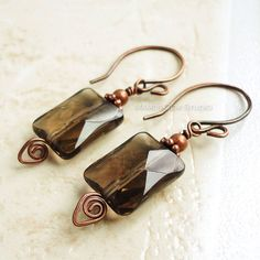 These are simple yet classy earrings which I carefully handcrafted, featuring Smoky Quartz semi-precious gemstone high quality faceted flat rectangle beads in a translucent mystical grayish brown hue. I have added solid copper tiny beads and spacers to accentuate, and wire-worked with my hand-formed spiral headpins to hang from my handmade copper ear-wires. All metal materials are genuine copper and have been hand-antiqued then polished in my studio for a lovely vintage look. Length: approx…