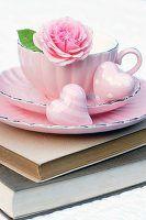 Rosafarbene Tasse auf Bücherstapel dekoriert mit Rosenblüte & Dekoherzen
