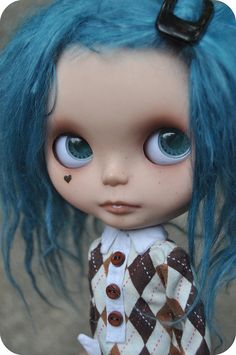 Blythe doll  marked with a heart shaped tattoo and blue hair.