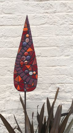 Glass garden mosaic Eastern Jewels- A rich combination of purple, red and orange jewel like colours. Looks stunning teamed with purple, orange or deep red flowers or foliage in the garden. Tear-drop shape. Approx size: 12cm x 40 cm Mounted onto a 1m metal pole which will rust naturally to give a rustic feel.  Serpentine design.