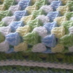 Beautiful baby blue, soft yellow and sage green crochet blanket.