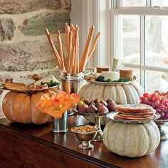Remove the stems from pumpkins and lay plates or platters on top to create a pretty display for Fall ~ Thanksgiving Buffet idea!