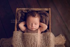 Just chilling! Gorgeous little newborn baby boy, relaxing in a crate filled with fluff. Love the hair!