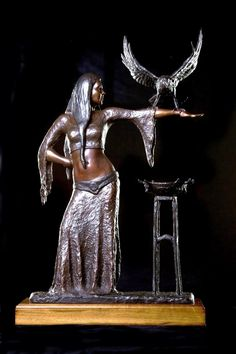 Morgan Le Fay: 570 mm high x 340 mm x 150 mm. The sculpture depicts Morgan Le Fay of the Arthurian legend.  She is the half sister of Arthur of the Round Table, a healer and a sorceress, pupil of Merlin.  The raven on her arm is her scout and her alter-ego.