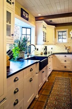 Country Kitchen with gas range, Undermount apron sink - black, Terra cotta tile floor, Exposed beam, Soapstone counters