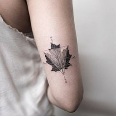 Maple leaf and compass tattoo on the back of the right arm.