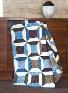 This fun, easy quilt features the spool quilt block in a brown and blue color scheme. Perfect your diagonal seams technique on this quilt project.