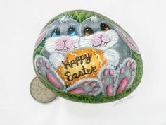 Easter painted rock  This hand painted Easter rock will be cherised by any child or adult for years to come.  This stone depicts two adorable gray bunnies holding a yellow/gold Easter egg. Happy Easter is already painted on the egg.  This rock is about 3.5 (9cm) long ,2.75 (7cm) wide