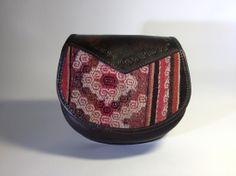 Middelgrote tas, geheel gemaakt van leer. De tas heeft een verstelbaar hengsel, een  binnenvak met apart ritsvak en een kleiner voorvak met rits. Bovendien is de tas gevoerd van binnen. De tas sluit met een drukknoop.  Op de voorkant is handgeweven doek verwerkt.  Afmeting: hoogte: 19 cm, breedte: 21 cm, diepte: 6 cm.   Uit: Copacabana Bolivia