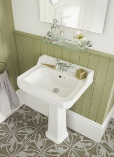 Panelling is perfect for a traditional bathroom and looks great when painted in muted colours such as this mid-green.  Give it a funky edge with patterned floor tiles.