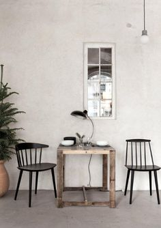 small table. rough. mismatched black chairs. white wash. grey floor. table lamp. window.