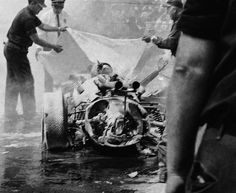 Eddie Sachs is covered with a tarp by track workers at Indianapolis. Sachs died on impact with Dave MacDonald's Mickey Thompson racer. This tragedy left me crying as I listened to it on the radio. I was just 11 years old and a fan of Dave MacDonald and the ever smiling Sachs.