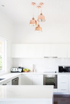 Bright all-white kitchen with white cabinents, dark wood floors, and rose gold pendant lights