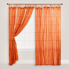 In a warm orange hue, our tie-top crinkle voilce curtains allow diffused light to enter the space while providing privacy and a soft update to your home decor. Use in the bedroom as a soothing accent or hang in multiples around a four-poster bed.