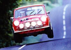 Mini Cooper Grabs Some Air. Contrary to some so-called experts, race cars go faster if their tires are actually touching the road. Red Mini Cooper, Mini Cooper Classic, Classic Mini, Classic Cars, Vintage Sports Cars, British Sports Cars, Vintage Cars, Audi, Porsche