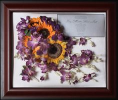 preserved cascade bouquet with invitation and boutonniere framed in a mahogany rectangle frame.
