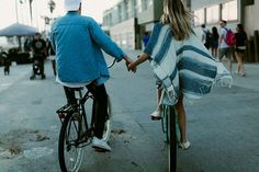 Cute back shot of hand holding while riding bikes on the boardwalk