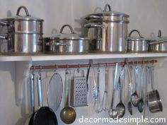 Organize a small kitchen by utilizing space. Build a shelf for pots, add copper piping and S hooks to hang utensils.