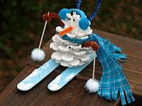 Pinecone Snowman  What you'll need - Pinecone, white, blue and black craft paint,  1 brown, and blue pipe cleaner, 2 med. blue pom poms, light blue felt,  blue scrap fabric, 2 med. white glittery pom poms, 2 toothpicks, 2 jumbo craft sticks, snow texture medium, hot glue gun, scissors