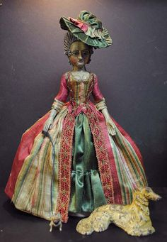 this is another wonderful French court doll. Beautiful 18th century striped fabric gown. I love the hat.