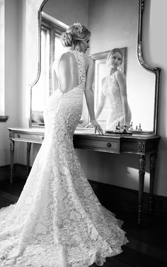 Read more about this vintage-style corded Lace over Lustre Satin fit-and-flare wedding dress with lace court train, an illusion halter neckline and a keyhole back.