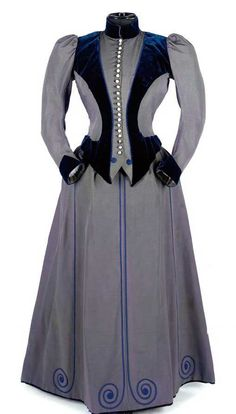 Corded silk walking dress, 1890s. Finely ribbed slate blue silk two-piece ensemble, embellished with midnight blue velvet panels and cord trim, fastening with a long row of pearlized buttons to the fitted bodice. Christie's.