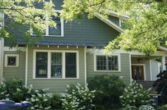 Cool neutrals layered.  Consider wavy siding, shingles and some stone in grays with red window trim.