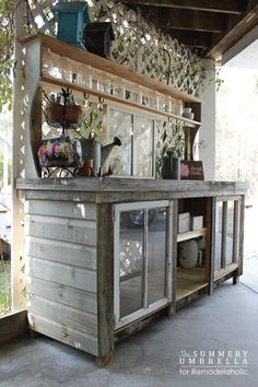 Really great potting bench.  Repurposed wood & old windows.  How pretty.