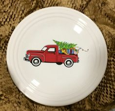 Fiesta® 'Belk Christmas Truck' Luncheon Plate features a red farm truck carrying a decorated Christmas Tree and wrapped presents in the center of a White Fiesta® Dinnerware Luncheon Plate. This 2017 Christmas plate was created exclusively for Belk Department Stores by Homer Laughlin China Company.