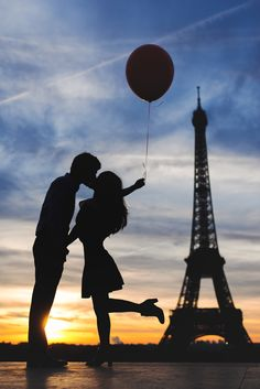 Silhouette of a couple kissing in front of the Eiffel Tower. Couple photo in…