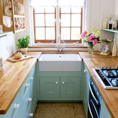 horseshoe small kitchen layout with aqua cabinets and wood countertops via House to Home