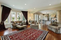 Elegant living room with large columns and hardwood floors.