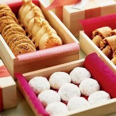 Package cookies in small wooden boxes lined with colorful tissue paper.